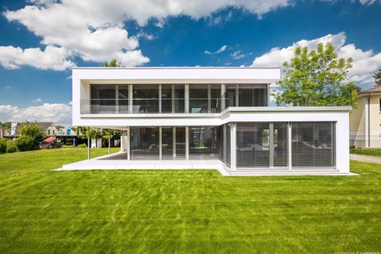 MusterHaus Bad Vilbel - Ein großes weißes Gebäude mit einer Wiese - Architektur - das Architekturhaus