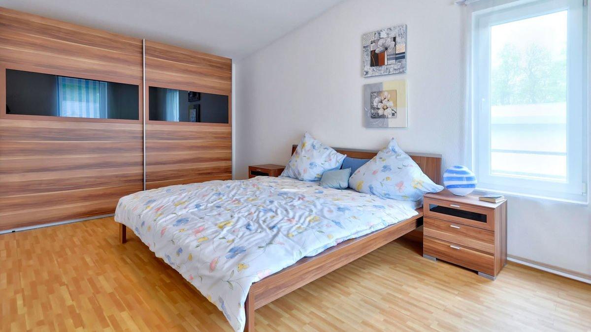 Musterhaus Frankfurt - Ein Schlafzimmer mit einem Bett und einem Fenster - Schlafzimmer