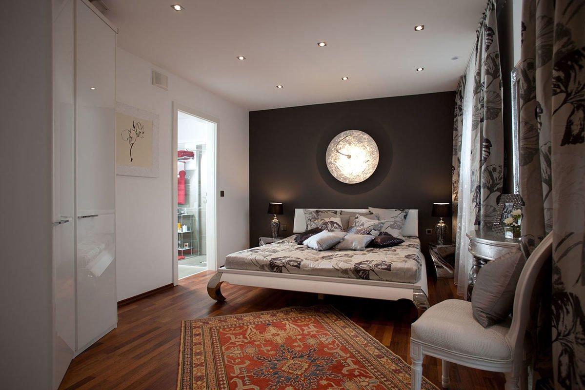 ELK Effizienzhaus 144 - Ein Raum mit einer Uhr auf einem Bett - ELK Fertighaus GmbH