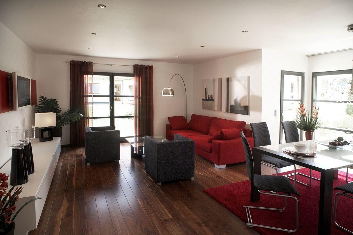 Musterhaus Valencia - Ein Wohnzimmer mit Möbeln und einem Flachbildfernseher - Rensch-Haus GmbH