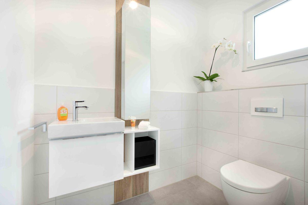 Musterhaus Fellbach - Ein weißes Waschbecken sitzt unter einem Fenster - Bad