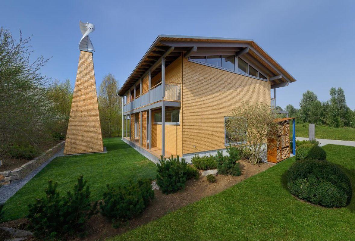 Alpenchic - Ein großes Backsteingebäude mit grünem Gras vor einem Haus - Bau-Fritz GmbH & Co. KG, seit 1896