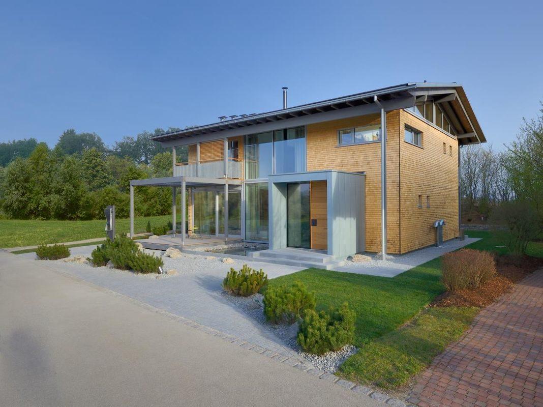 Alpenchic - Ein großes Backsteingebäude mit Gras vor einem Haus - Bau-Fritz GmbH & Co. KG, seit 1896