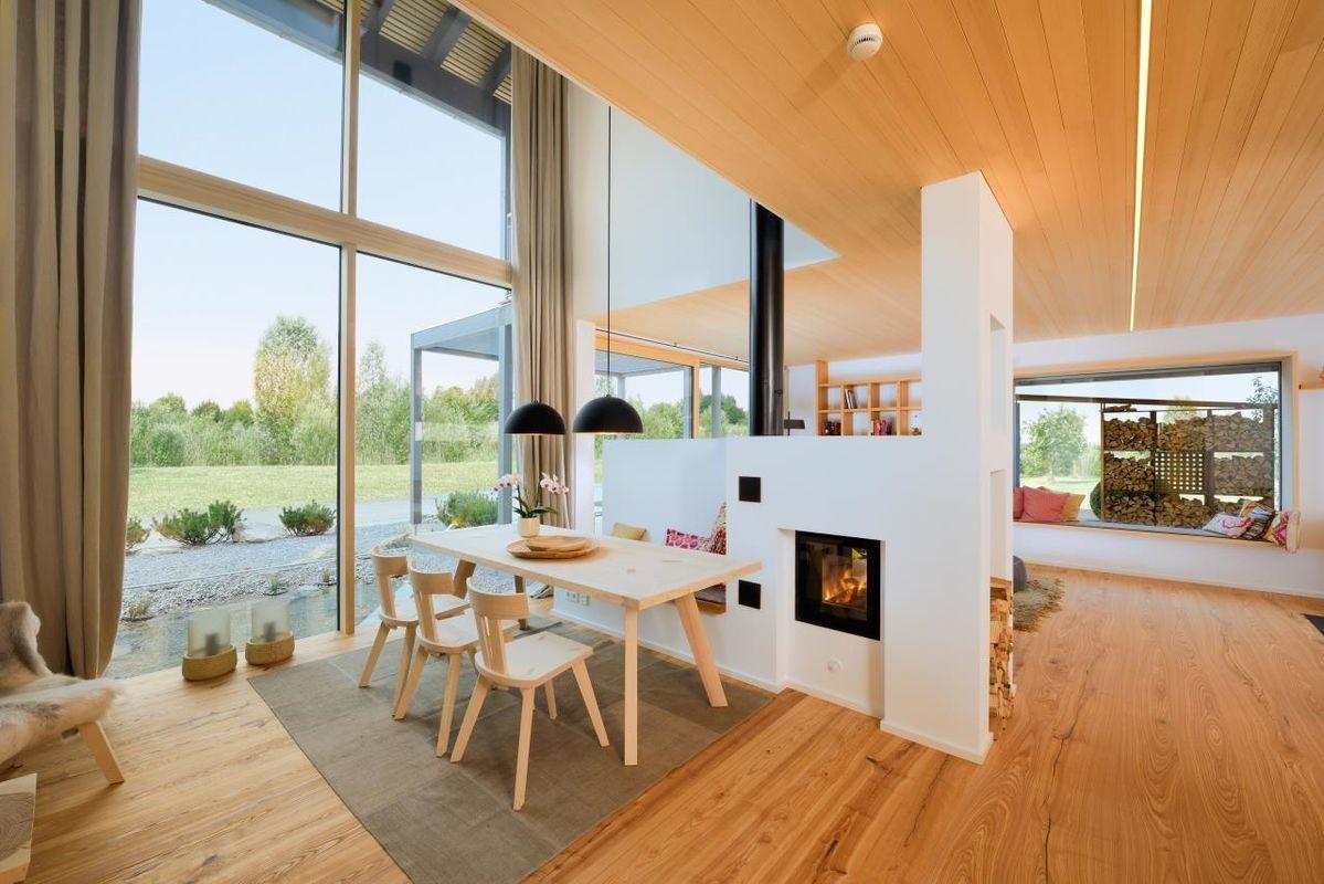 Alpenchic - Eine Ansicht eines mit Möbeln gefüllten Wohnzimmers und eines großen Fensters - Bau-Fritz GmbH & Co. KG, seit 1896