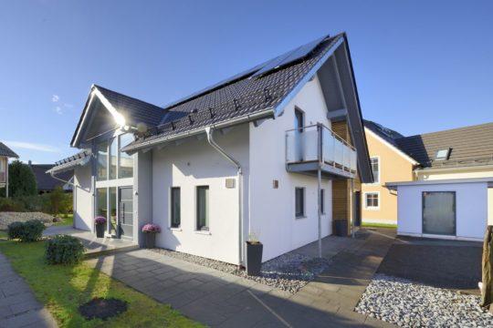 Musterhaus Poing-Grub - Ein großes Backsteingebäude mit Gras vor einem Haus - Haus