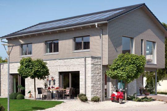 Energieplus Haus Poing - Ein großes Backsteingebäude mit Gras vor einem Haus - SchwörerHaus KG Musterhaus Poing