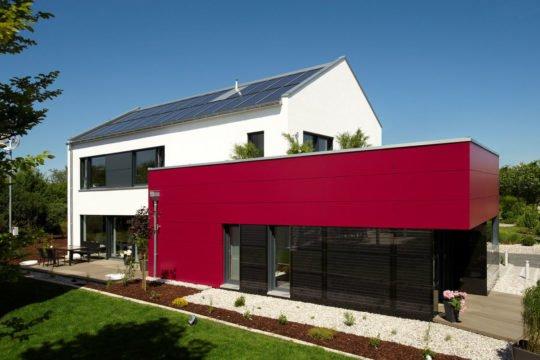Energie-Plus-Haus Generation X - Ein großes Backsteingebäude mit Gras vor einem Haus - Haus