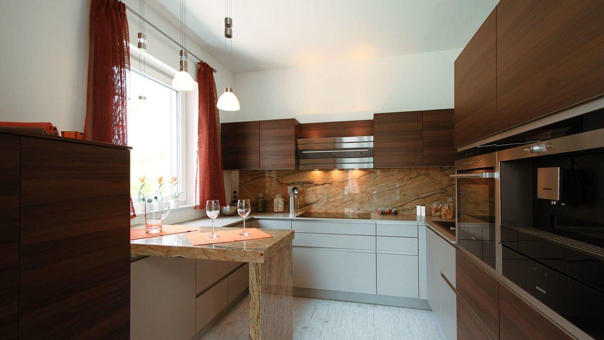 Passivhaus EOS 173 - Eine moderne Küche mit Edelstahlgeräten und Holzschränken - Klassische Küche