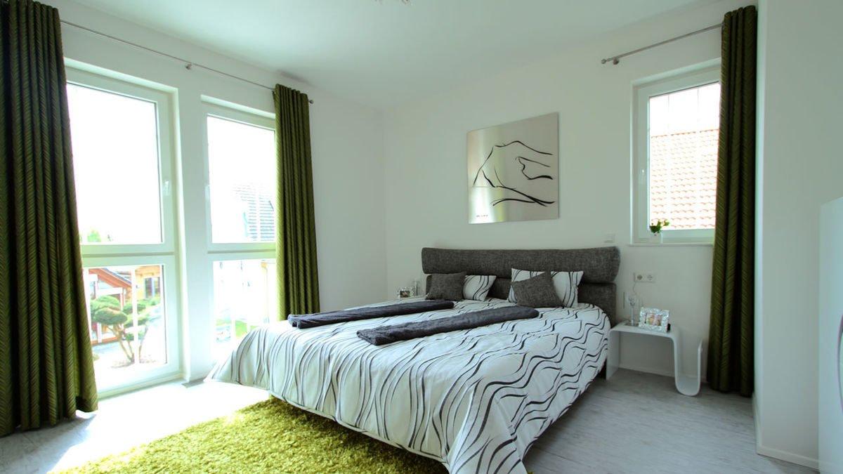Passivhaus EOS 173 - Ein Schlafzimmer mit einem Bett und einem Fenster - Schlafzimmer