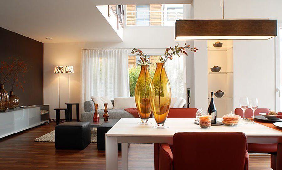 Musterhaus Suhr 179 - Ein Wohnzimmer mit Möbeln und Vase auf einem Tisch - Interior Design Services