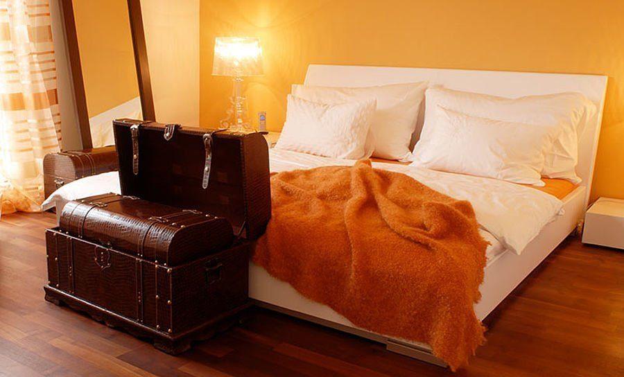 Musterhaus Suhr 179 - Ein Schlafzimmer mit einem Bett und einem Schreibtisch in einem Raum - Haas Fertigbau GmbH