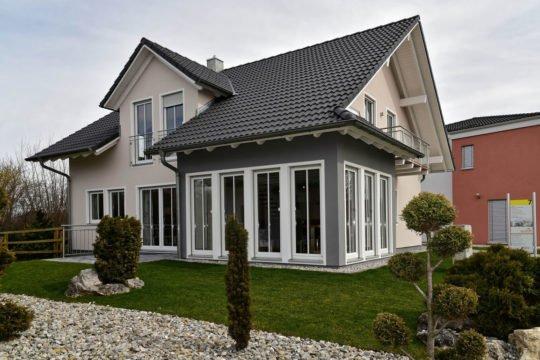 Musterhaus Poing G 154 - Ein kleines haus im hintergrund - Haas Haus - Fertighaus MH Poing G 154 als Musterhaus