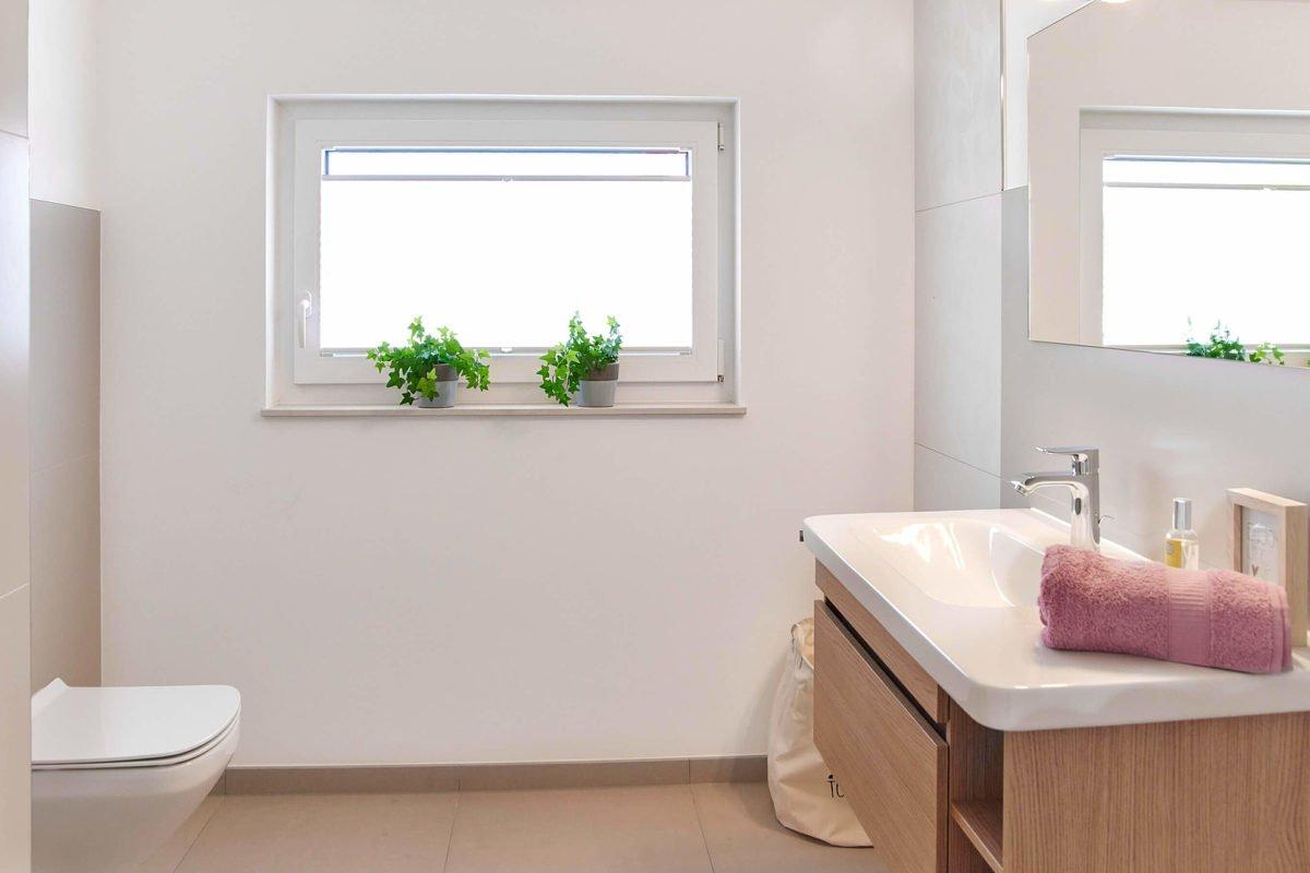 Musterhaus Mannheim - Ein weißes Waschbecken sitzt unter einem Fenster - Bad