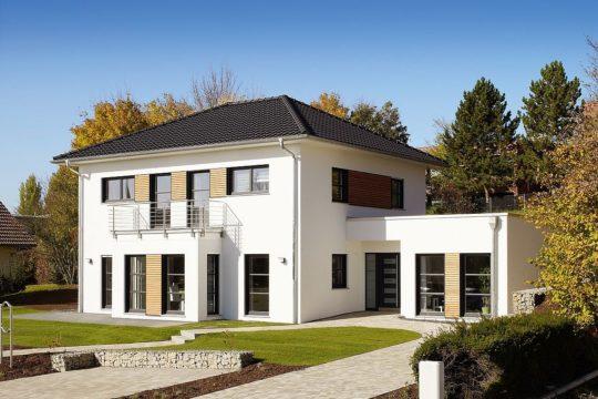 Musterhaus Orlando - Ein Haus mit Büschen vor einem Backsteingebäude - Rensch-Haus GmbH