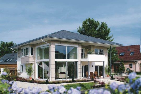 Villa mit Aussicht - Ein haus mit büschen vor einem gebäude - WeberHaus GmbH & Co. KG