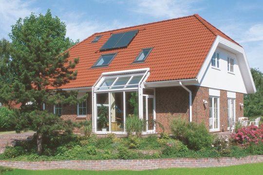 Glücksburg – Das 1Liter-Haus - Ein großes Backsteingebäude mit Gras vor einem Haus - Danhaus GmbH