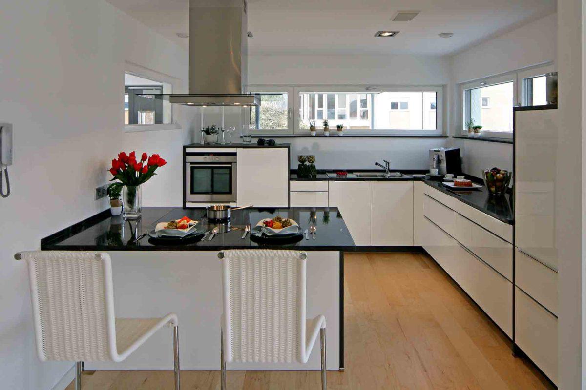 Musterhaus Erlangen - Eine Küche mit einem Tisch in einem Raum - Fertighaus Weiss