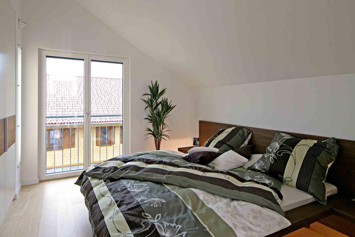Musterhaus Erlangen - Ein Schlafzimmer mit einem großen Bett in einem Raum - Fertighaus Weiss