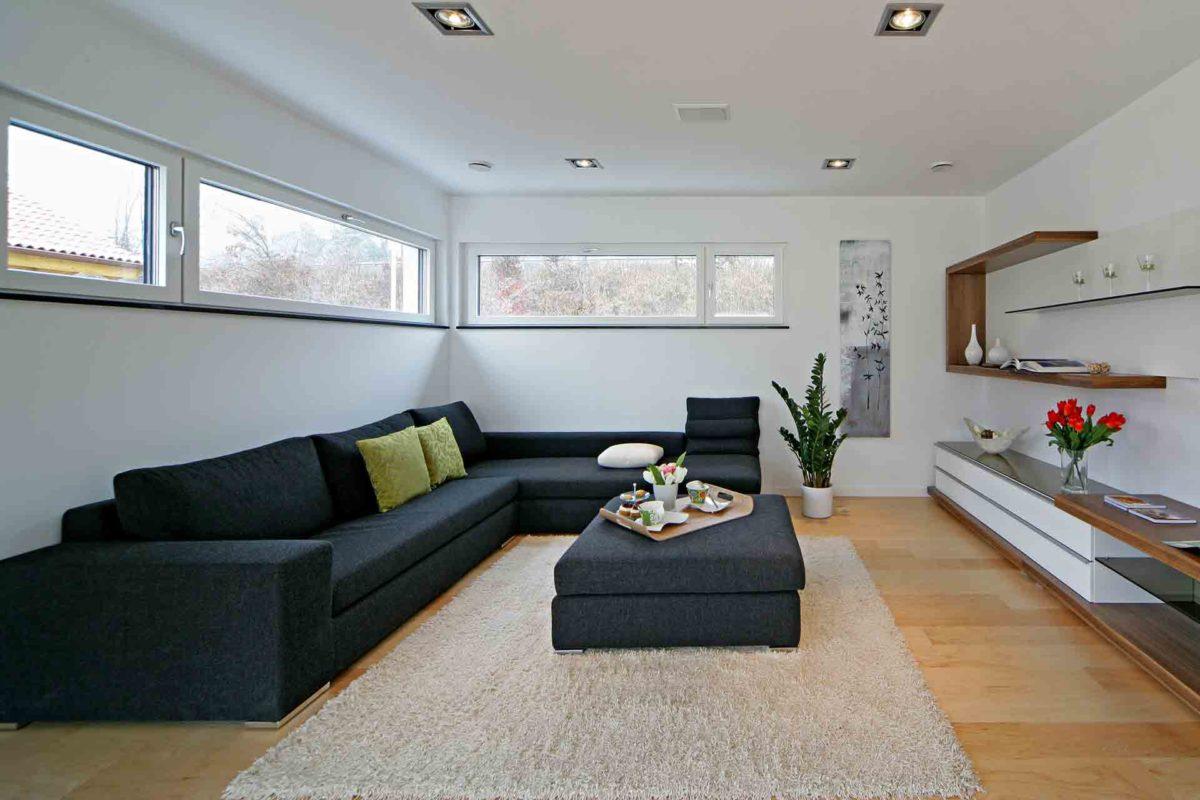 Musterhaus Erlangen - Ein Wohnzimmer mit Möbeln und einem Flachbildfernseher - Fertighaus Weiss