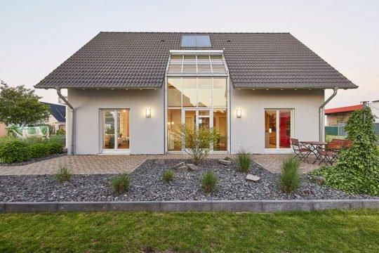 Musterhaus Evita - Ein Haus mit Bäumen im Hintergrund - Haus