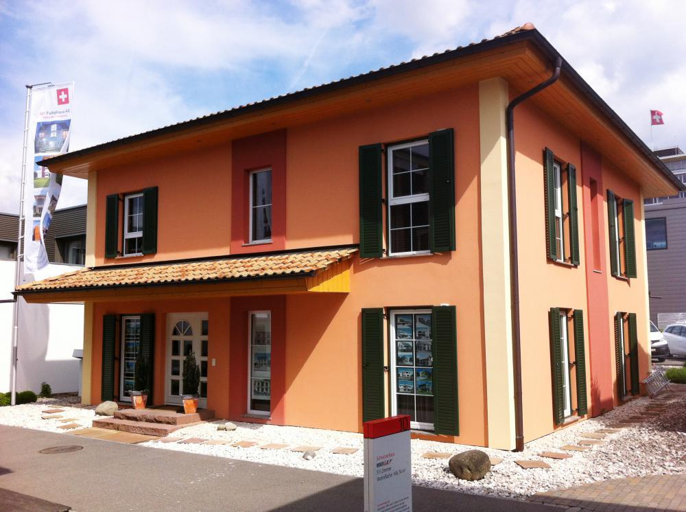 Musterhaus Tosca - Ein Haus, das an der Seite eines Gebäudes geparkt ist - Haus