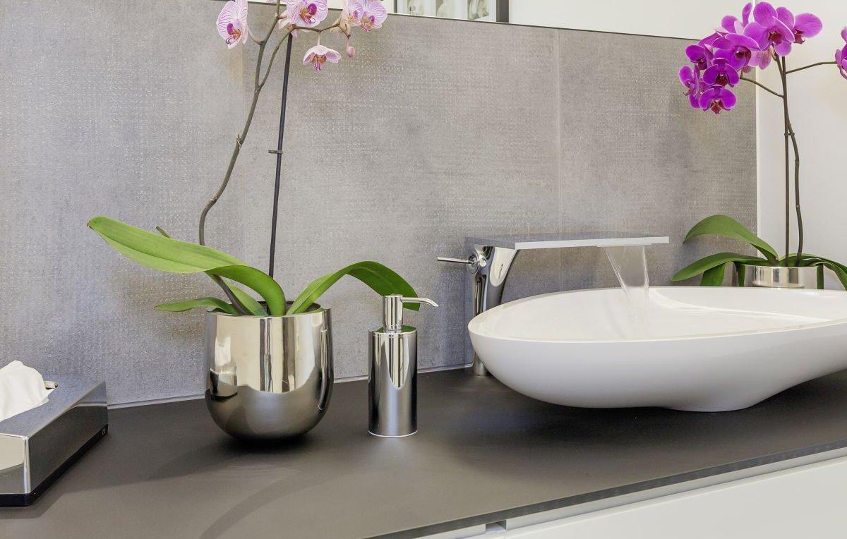 Musterhaus Köln - Ein weißes Waschbecken neben einer Blumenvase auf einem Tisch - Bad