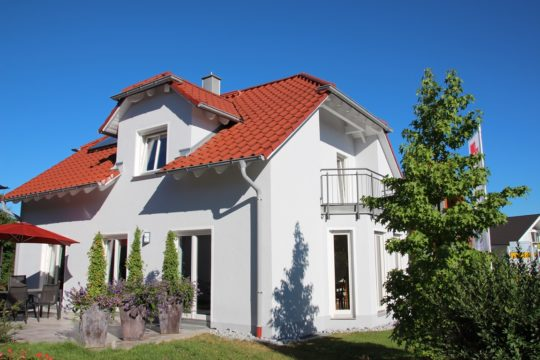 Massivhaus Poing - Ein Haus mit Bäumen im Hintergrund - MVS Ziegelbau GmbH