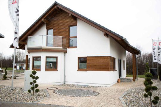 Musterhaus Poing - Ein Haus, das an der Seite eines Gebäudes geparkt ist - Haus