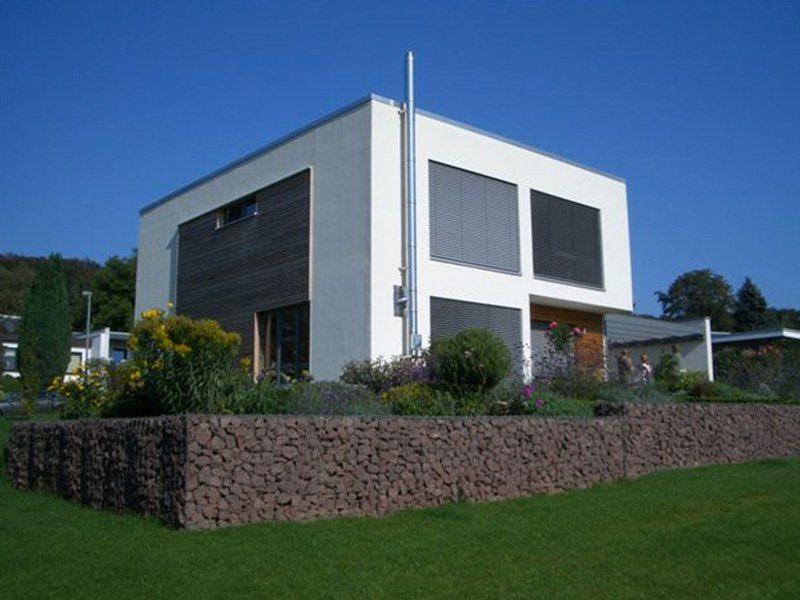 Bauhaus - Ein großes Backsteingebäude mit Gras vor einem Haus - Haus