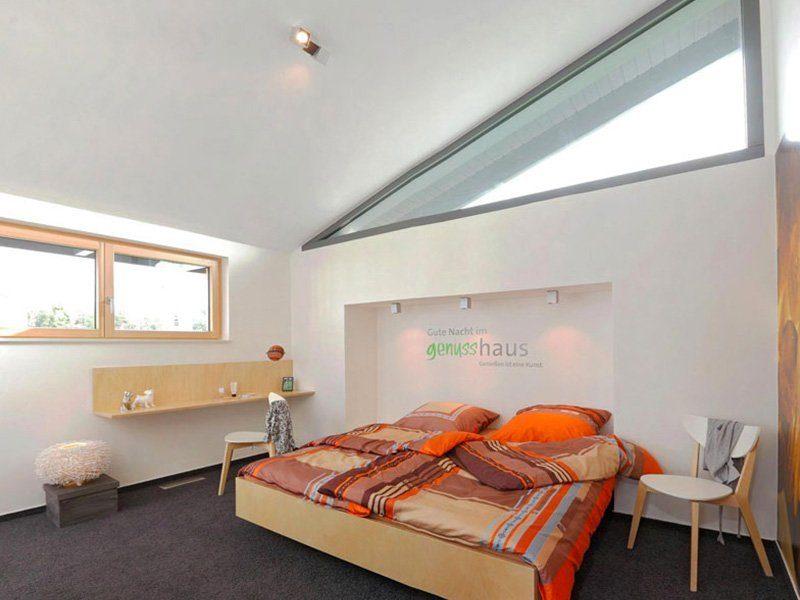 Das Genuss – Musterhaus Köln - Ein Schlafzimmer mit einem Bett und einem Schreibtisch in einem Raum - Haus