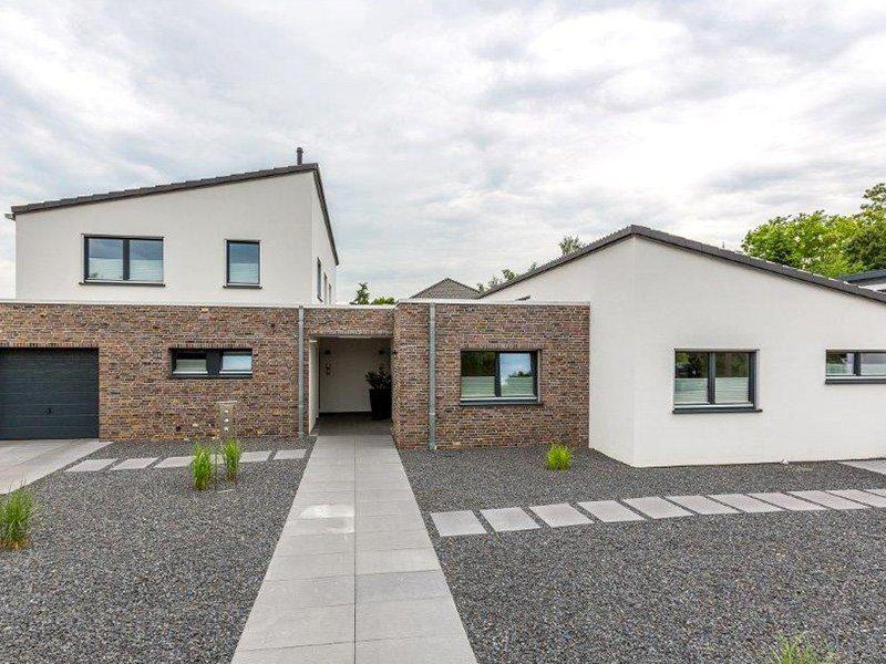 Generationenhaus - Ein Haus, das an der Seite eines Gebäudes geparkt ist - Haus