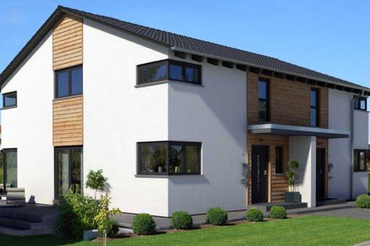 Kubus Doppelhaushälfte - Ein großes Backsteingebäude mit Gras vor einem Haus - Haus
