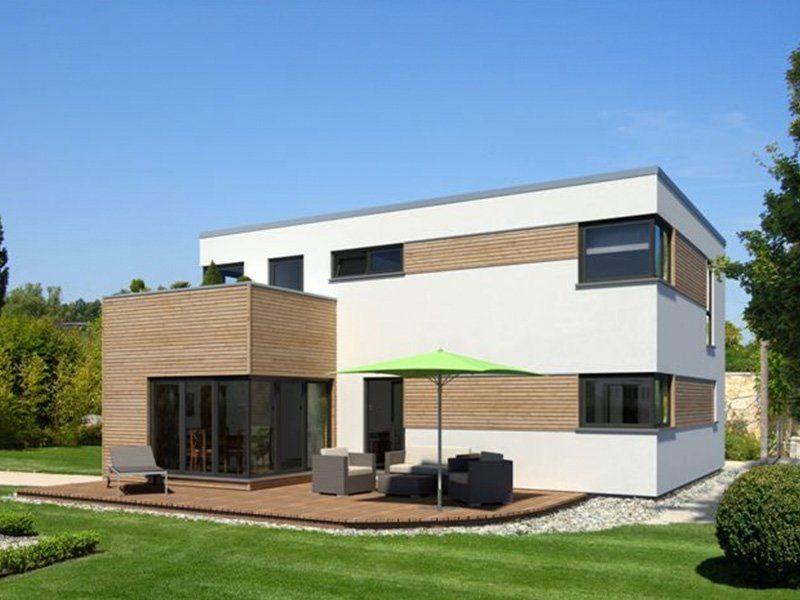 Kubus Edition Holz 65 - Ein großes Backsteingebäude mit Gras vor einem Haus - Würfelhaus