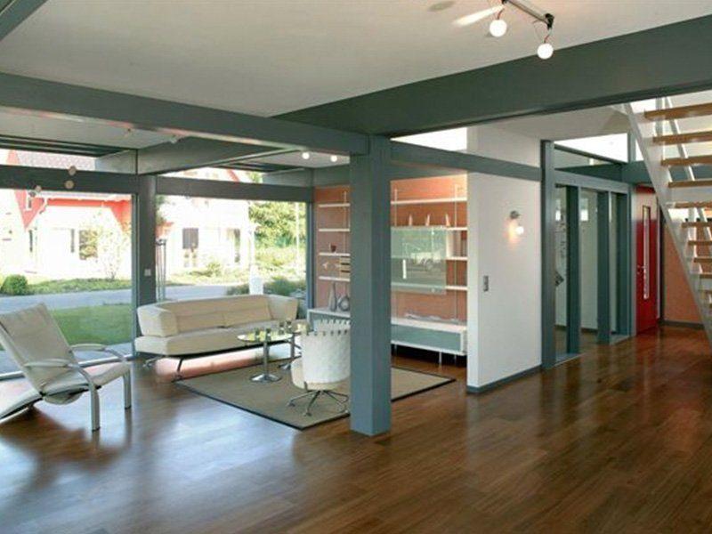Musterhaus Ästhetik Hannover - Ein Wohnzimmer mit Möbeln und einem großen Fenster - Rahmenkonstruktion von Gebäuden