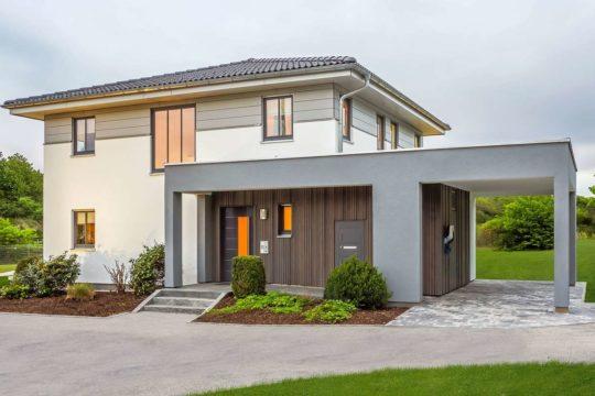 Musterhaus Falkenberg 150 - Ein Haus, das ein Schild an der Seite eines Gebäudes hat - HAAS GmbH & Co. Beteiligungs KG