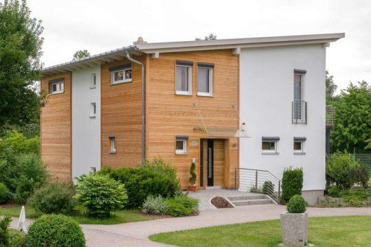 Musterhaus Falkenberg 168 - Ein großes Backsteingebäude mit Gras vor einem Haus - Fertighaus