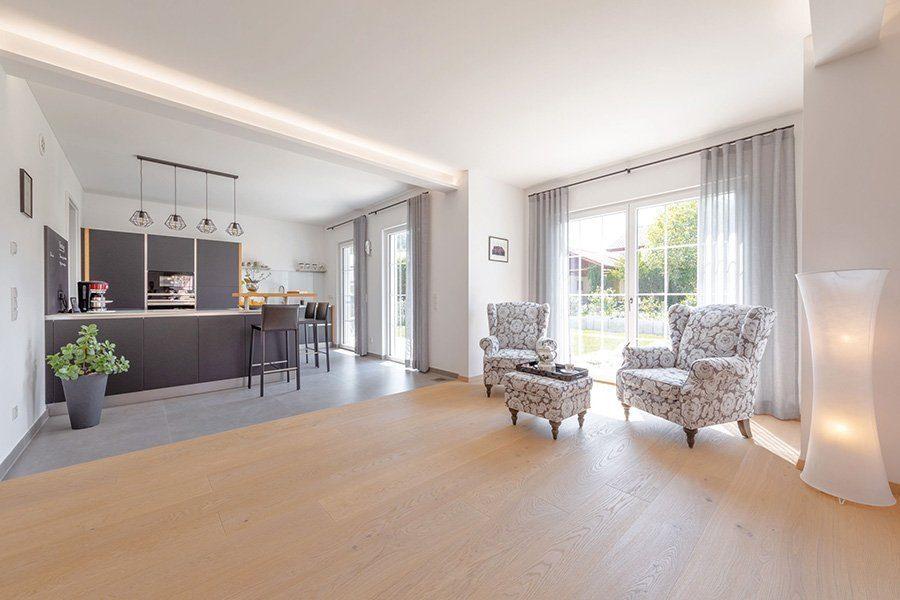 Vitalhaus Albaching - Ein Wohnzimmer mit Möbeln und einem großen Fenster - Regnauer Fertigbau GmbH & Co. KG