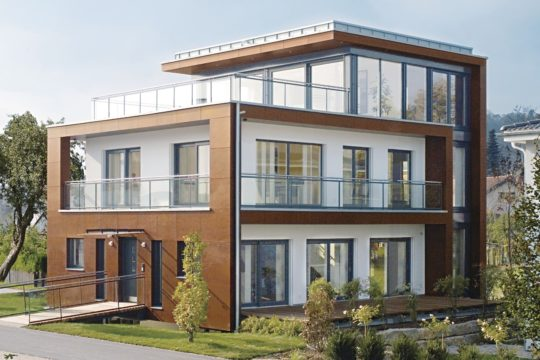 Ausstellungshaus Minergie - Ein großes Backsteingebäude mit Gras vor einem Haus - WeberHaus GmbH & Co. KG