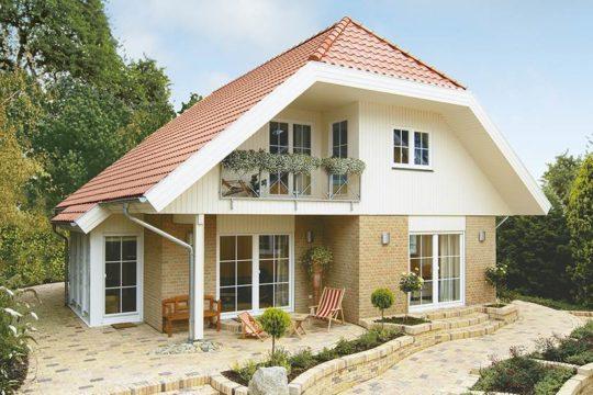 Kolding – das 1Liter-Haus! - Ein Haus mit Büschen vor einem Backsteingebäude - Danhaus GmbH