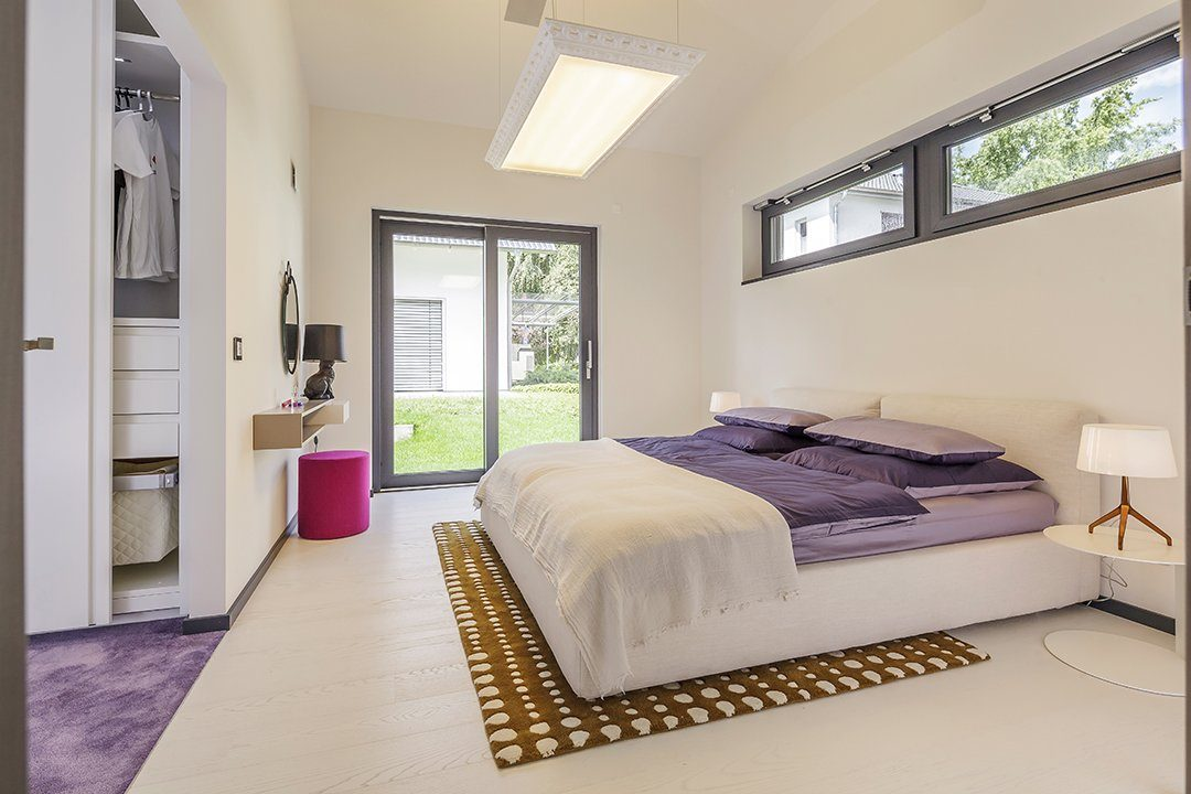 Musterhaus Fellbach Open - Ein Schlafzimmer mit einem Bett und einem Tisch in einem Raum - Tröster