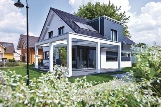 Energiesparhaus - Ein haus mit büschen vor einem gebäude - Haus