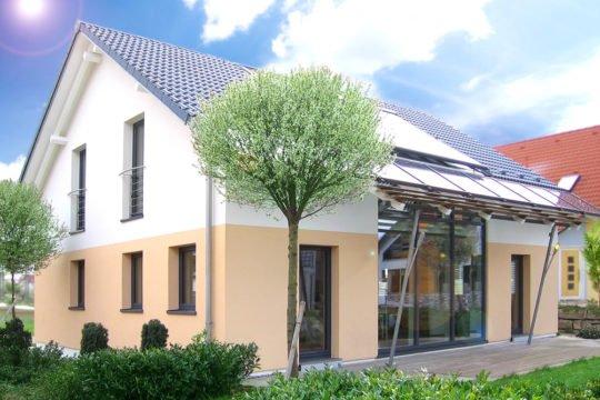 Musterhaus Fellbach - Ein haus mit büschen vor einem gebäude - Haus