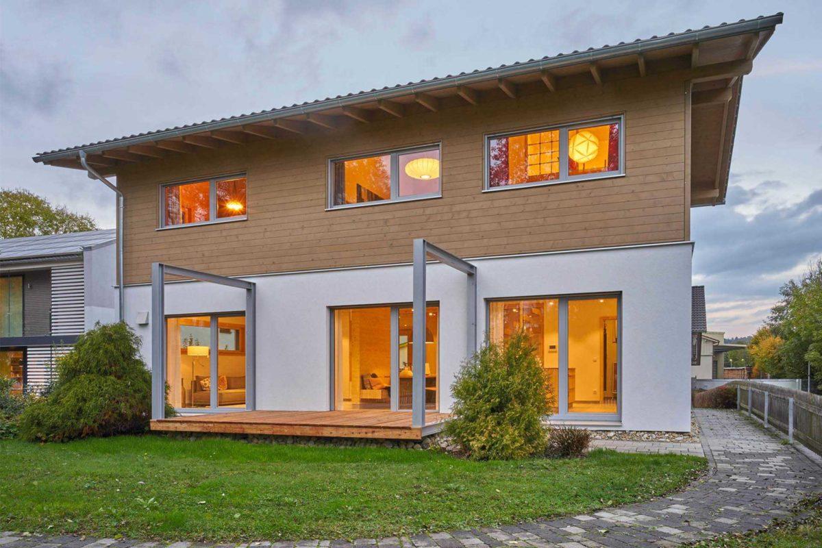 Musterhaus Casa Vita - Ein großes Backsteingebäude mit Gras vor einem Haus - Merklingen
