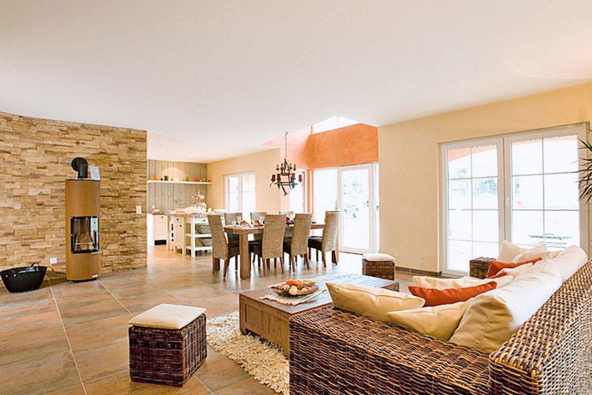 Musterhaus Tosca - Ein Wohnzimmer mit Möbeln und einem großen Fenster - Fertighaus