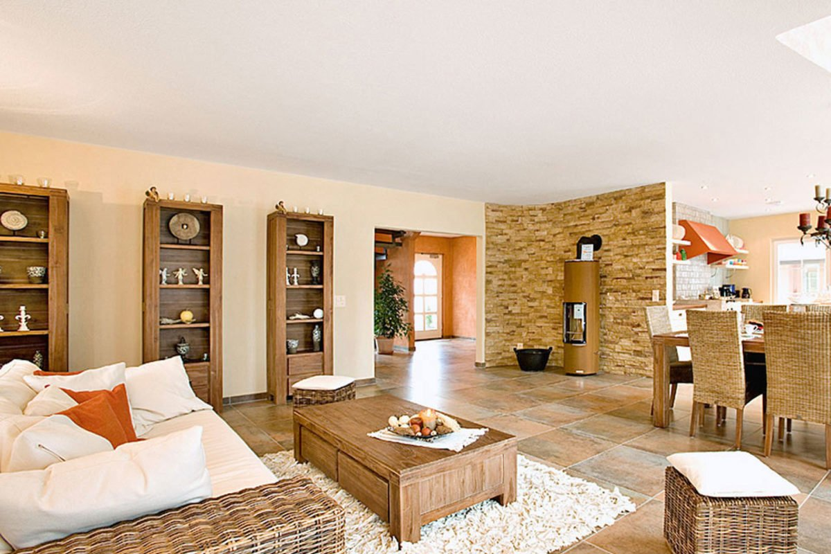 Musterhaus Tosca - Ein Wohnzimmer mit Möbeln und einem Kamin - Swissbau Fertighaus AG