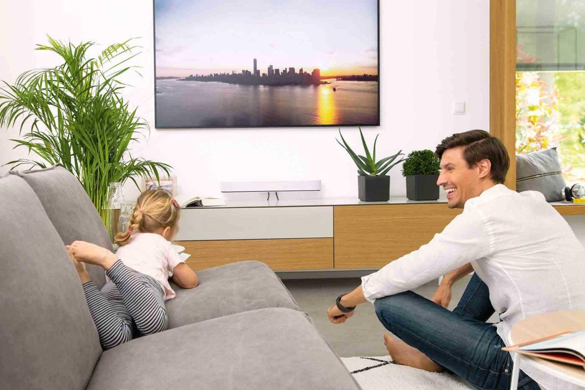 Musterhaus Sunshine - Eine Person, die in einem Wohnzimmer sitzt und ein Videospiel spielt - WeberHaus
