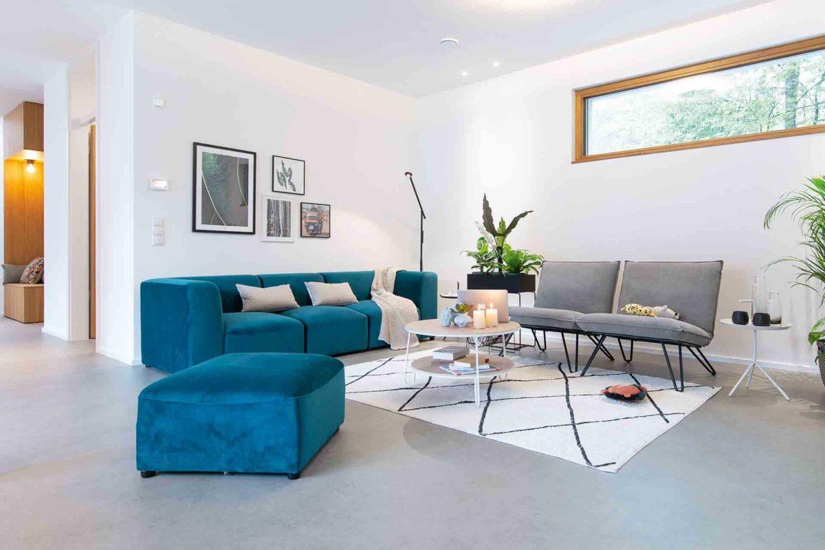 Musterhaus Sunshine - Ein Wohnzimmer mit Möbeln und einem großen Fenster - Welt des Lebens