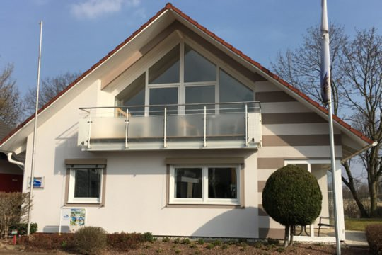 Musterhaus Mannheim - Eine Person, die vor einem Haus sitzt - Haus