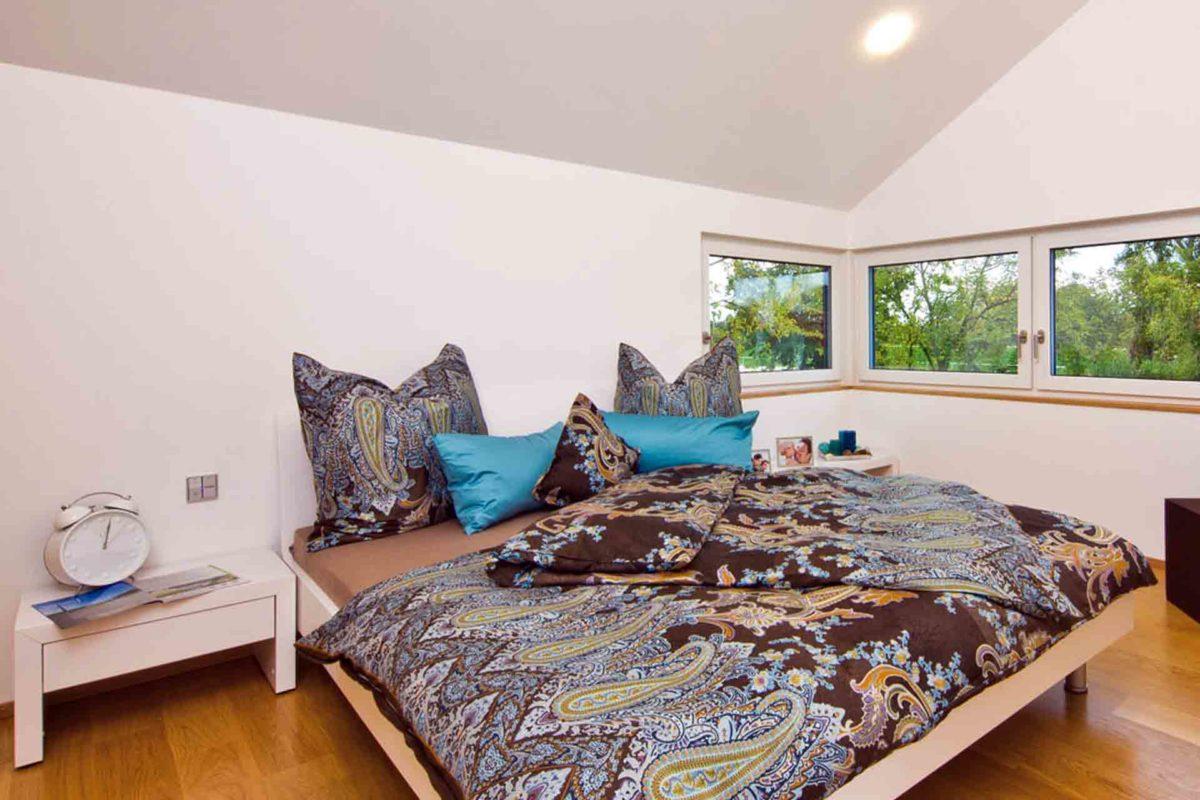 Musterhaus Future - Ein Schlafzimmer mit einem Bett in einem Raum - Fertighaus