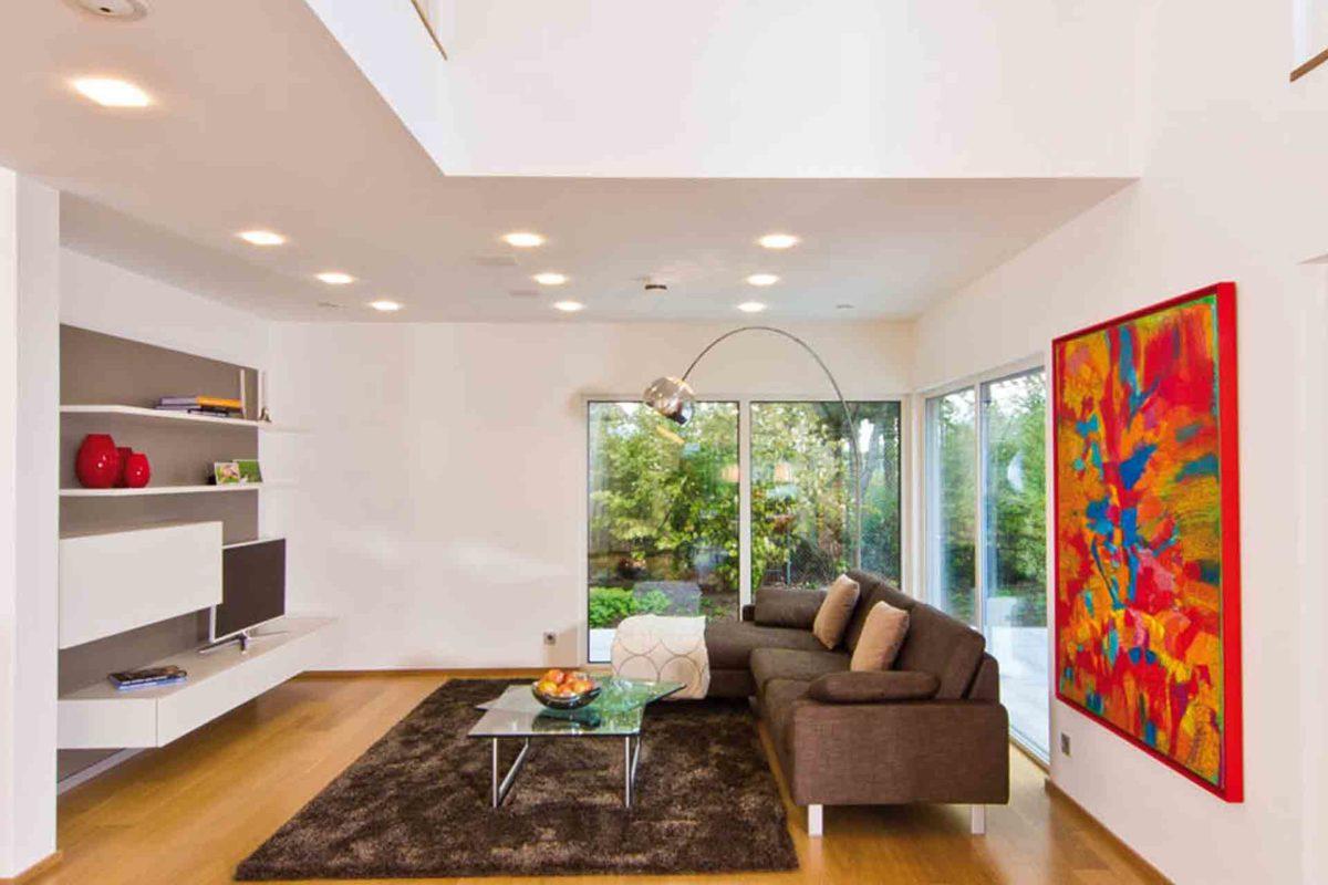 Musterhaus Future - Ein Wohnzimmer mit Möbeln und einem Kamin - Fertighaus